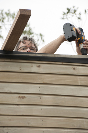 Hispanic man using cordless drill on rooftop