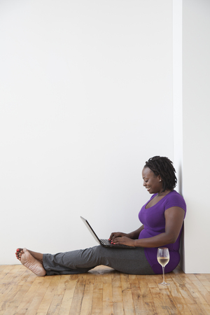 Black woman drinking wine and using laptop on floor