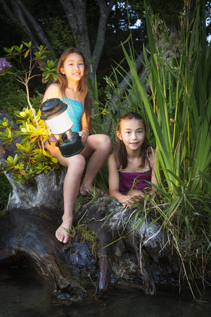 Mixed race sisters sitting on riverbank with lantern