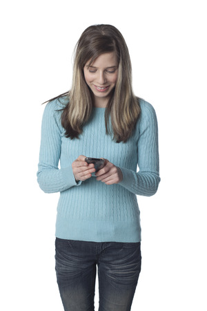 Caucasian teenager text messaging on cell phone