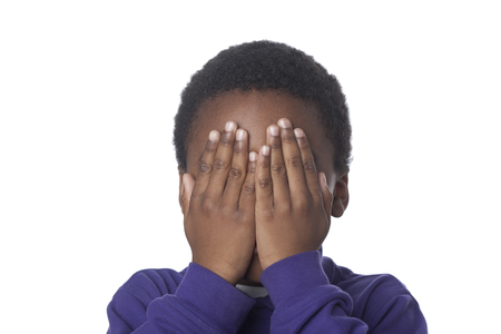 Mixed race boy covering face Stock Photo