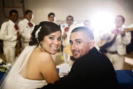 Hispanic bride and groom at wedding reception