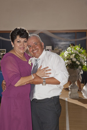 Hispanic couple dancing at wedding reception Stock Photo
