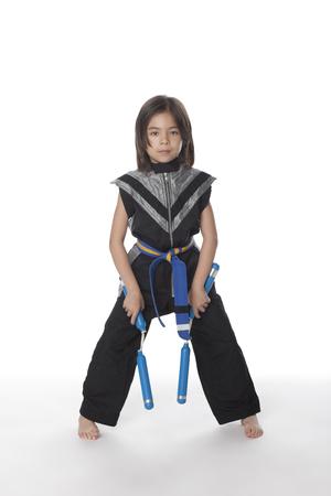 Mixed race girl in ninja outfit with nunchakus