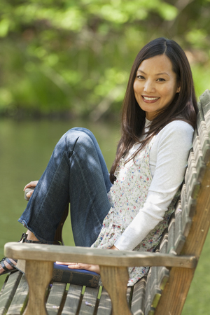 Asian woman sitting on bench in park