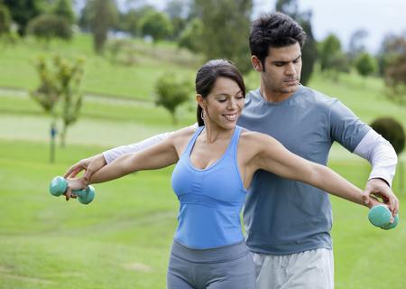 Hispanic man helping woman with hand weights