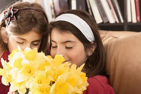 Hispanic girls smelling flowers