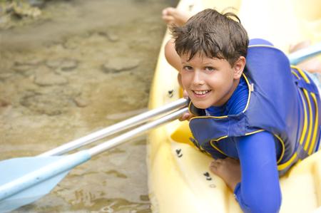 Hispanic boy sitting in canoe