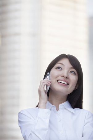 Smiling Chinese businesswoman talking on cell phone