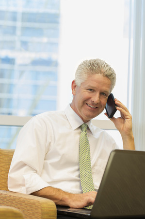 Caucasian businessman using laptop and cell phone