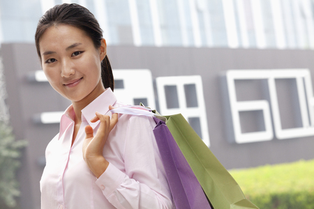 Chinese businesswoman carrying shopping bags Stock Photo