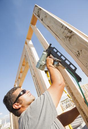Caucasian man using nail gun on frame
