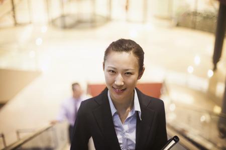 Chinese businesswoman riding escalator Stock Photo