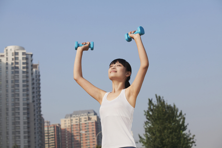 Chinese woman lifting hand weights Stock Photo