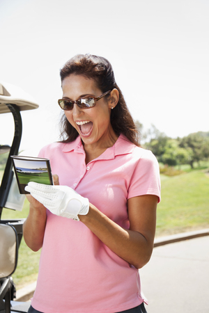 Woman keeping score during golf game Stock Photo