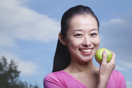 Chinese woman eating green apple