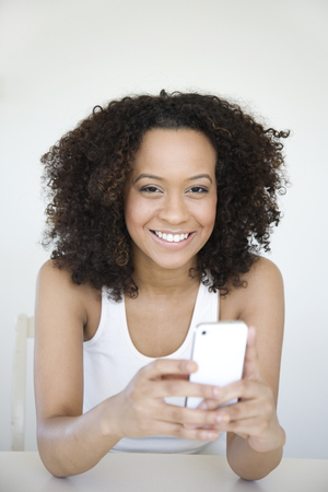 Hispanic woman text messaging on cell phone Stock Photo