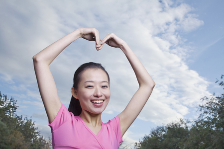 Chinese woman with arms raised making heart-shape Stock Photo