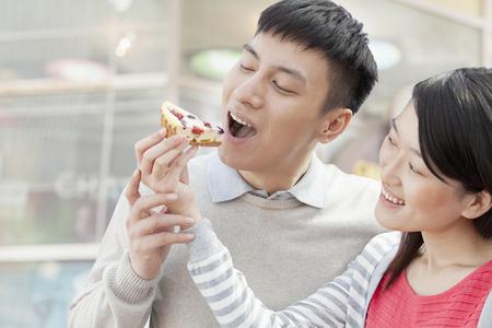 Chinese woman feeding pie to boyfriend