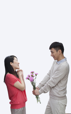 Chinese man giving girlfriend bouquet of flowers Stock Photo