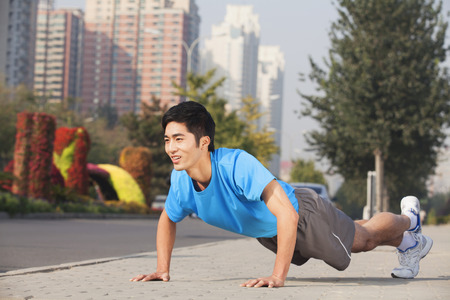 Chinese man doing push-ups in city Stock Photo