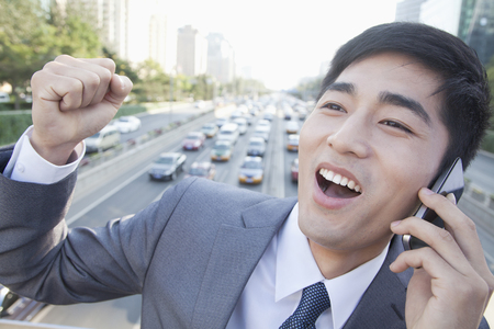 Chinese businessman on overpass talking on cell phone