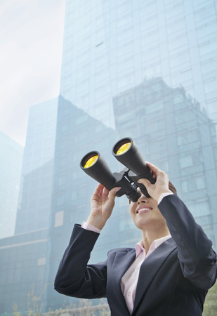 Chinese businesswoman using binoculars