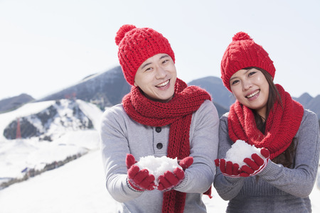 Chinese couple in snow wearing scarves and caps