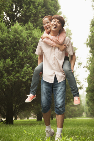 Chinese man carrying girlfriend piggyback