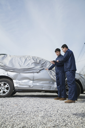 Chinese men looking at wrecked, covered car Stock Photo