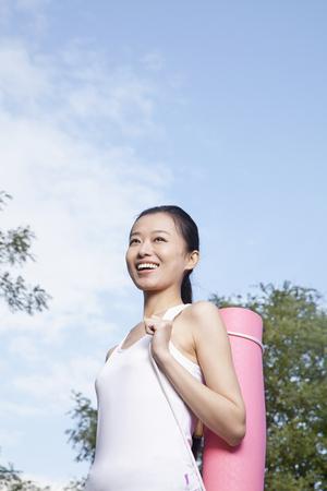 Chinese woman carrying yoga mat Stock Photo