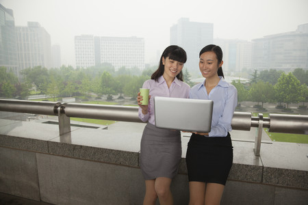 Chinese businesswomen using laptop outdoors Stock Photo