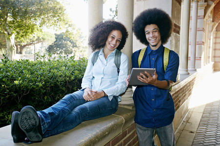 Mixed race college students with digital tablet Banco de Imagens