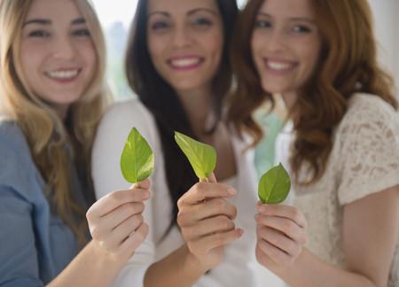 Smiling women holding green leaves