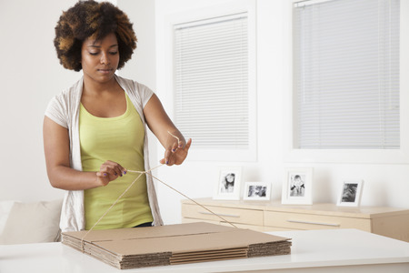 African American woman wrapping flat cardboard boxes