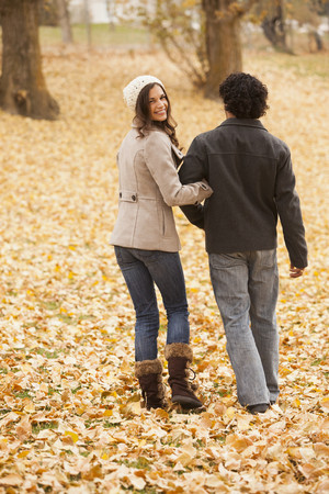 Couple walking in autumn leaves Stock Photo - 107910443