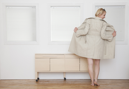 Nude Caucasian woman wearing trench coat