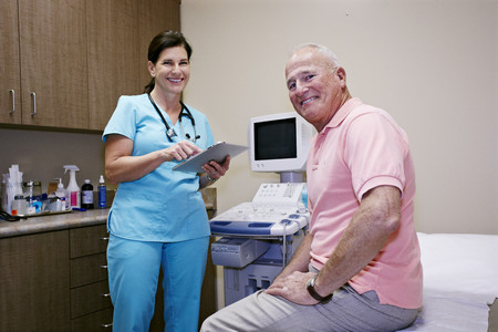 Caucasian nurse and patient smiling in office Stock Photo