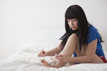 Chinese woman painting toenails on bed Stock Photo