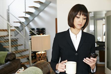 Mixed race businesswoman having coffee