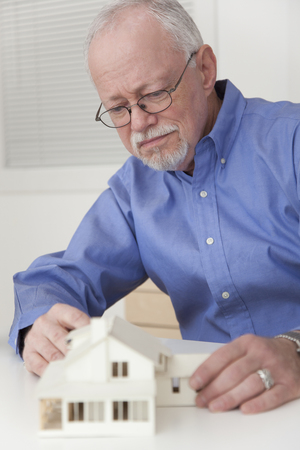 Caucasian businessman working on model of house Stock Photo