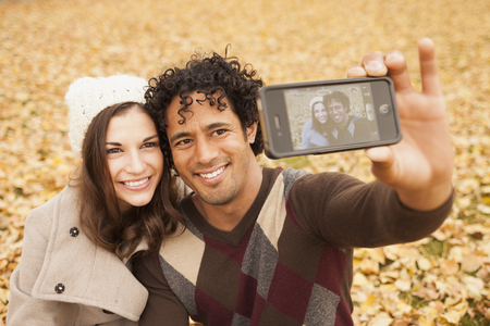 Couple taking picture of themselves in autumn leaves Stock Photo