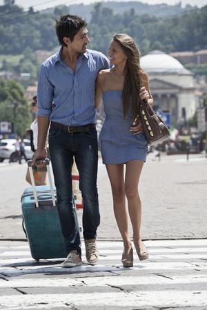 Caucasian couple pulling luggage