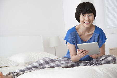 Chinese woman using tablet computer on bed Stock Photo
