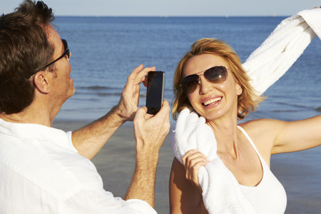 Caucasian man taking pictures of girlfriend on beach Stock Photo