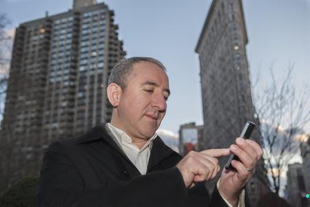 Hispanic businessman using cell phone in city