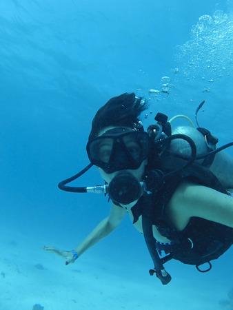 Hispanic woman scuba diving Stock Photo
