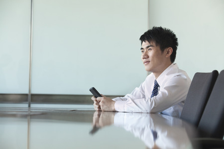 Chinese businessman holding cell phone in conference room Stock Photo