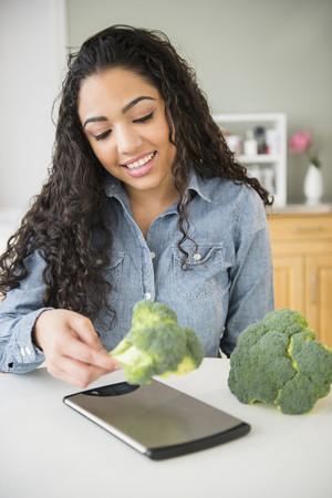 Hispanic woman weighing broccoli in kitchen