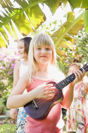 Caucasian girl playing ukulele outdoors